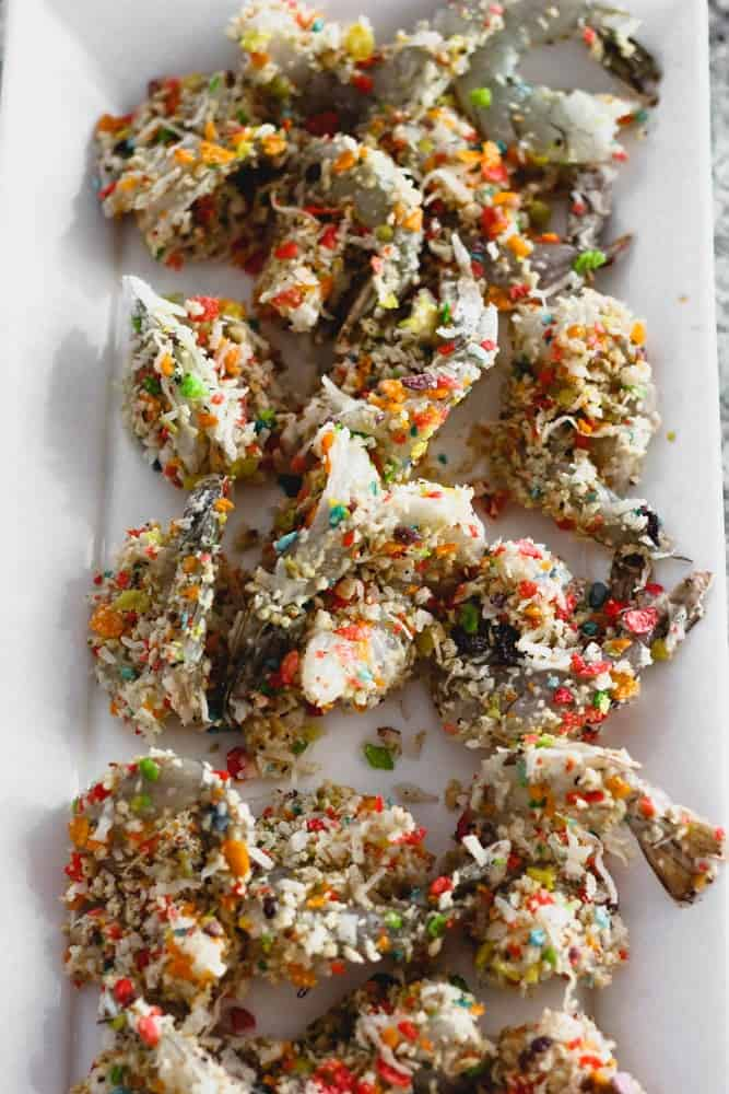 uncooked tail-on shrimp crusted in crushed multicolored cereal on a white platter