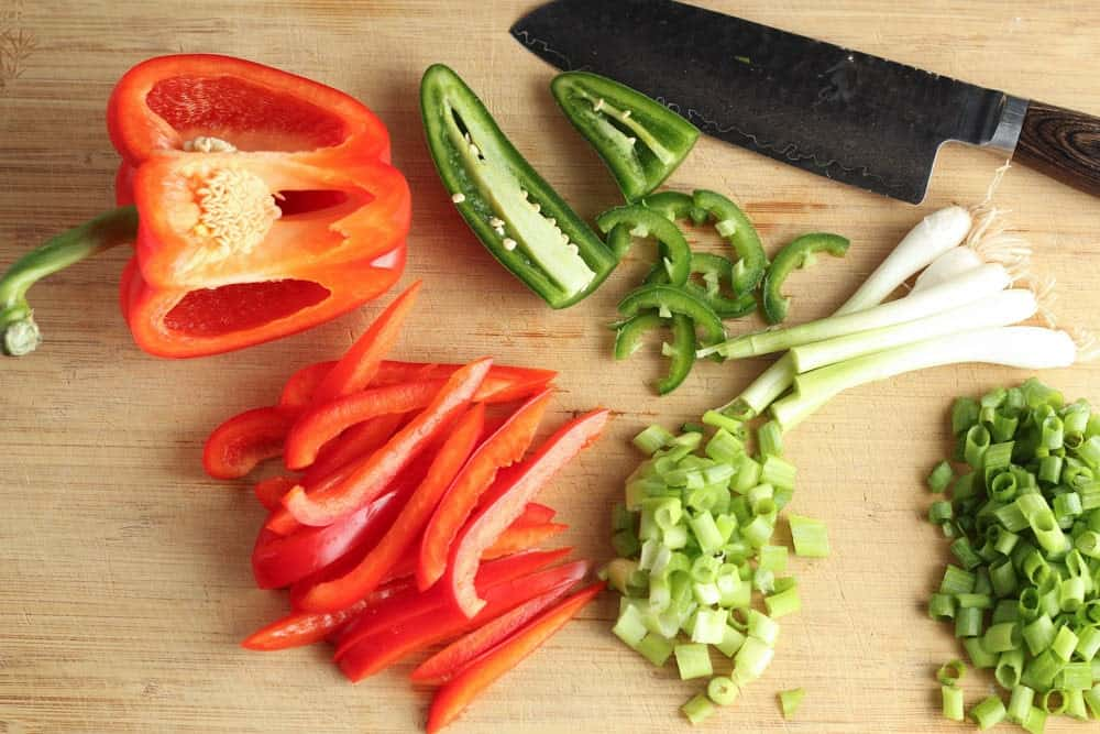 wooden cutting board with a silver knife and chopped green onions, sliced jalapenos and red bell pepper strips