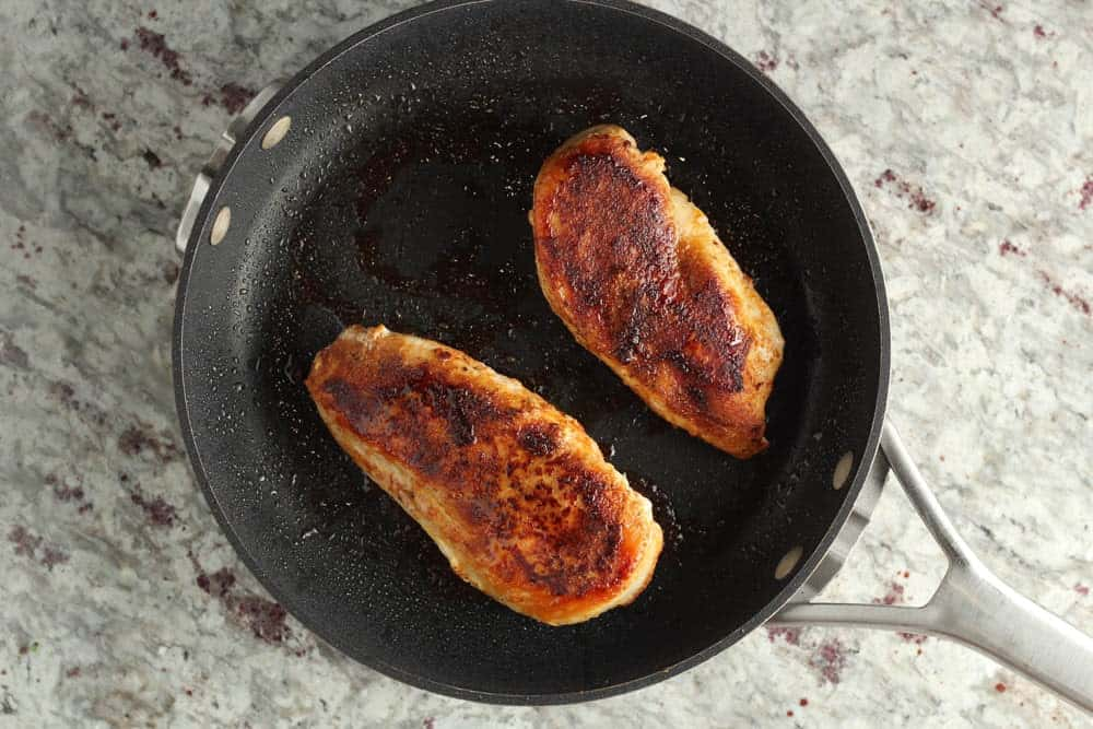 seasoned chicken breasts cooked in a dark saute pan
