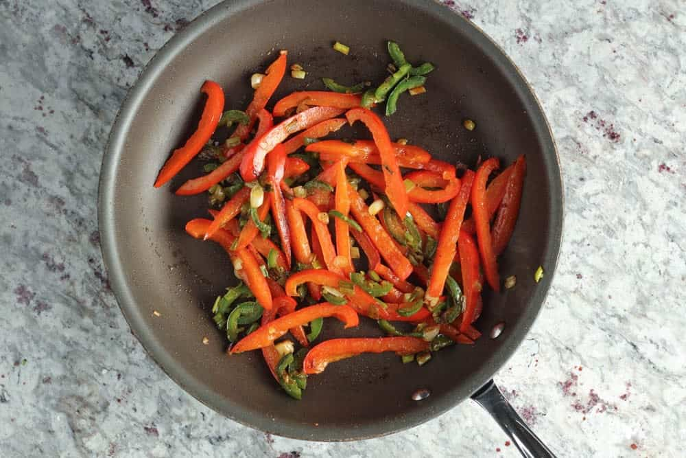 strips of red bell pepper cooking in a dark saute pan