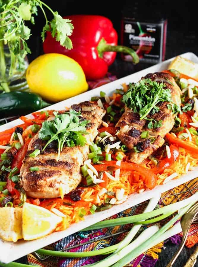 white rectangular plate filled with orange rice topped with strips of red bell pepper, green onion pieces, sliced chicken breast and cilantro