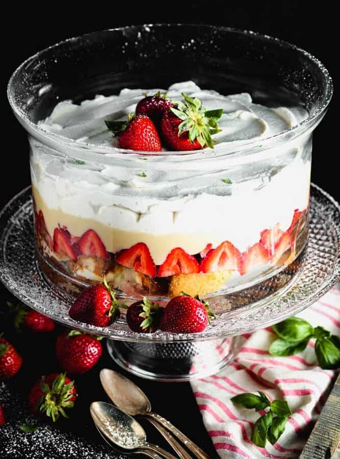 Clear round glass dish filled with layers of angel food cake, bright red strawberries, pale yellow vanilla pudding and white whipped cream topped with three whole strawberries on a clear glass pedestal with a pink and white napkin and four antique silver spoons