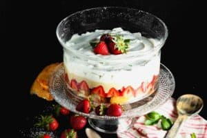Clear round glass dish filled with layers of angel food cake, bright red strawberries, pale yellow vanilla pudding and white whipped cream topped with three whole strawberries on a clear glass pedestal with a pink and white napkin and a brown wooden spoon