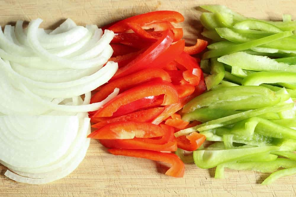 white onion and bright red and green bell peppers thinly sliced on a light wooden cutting board