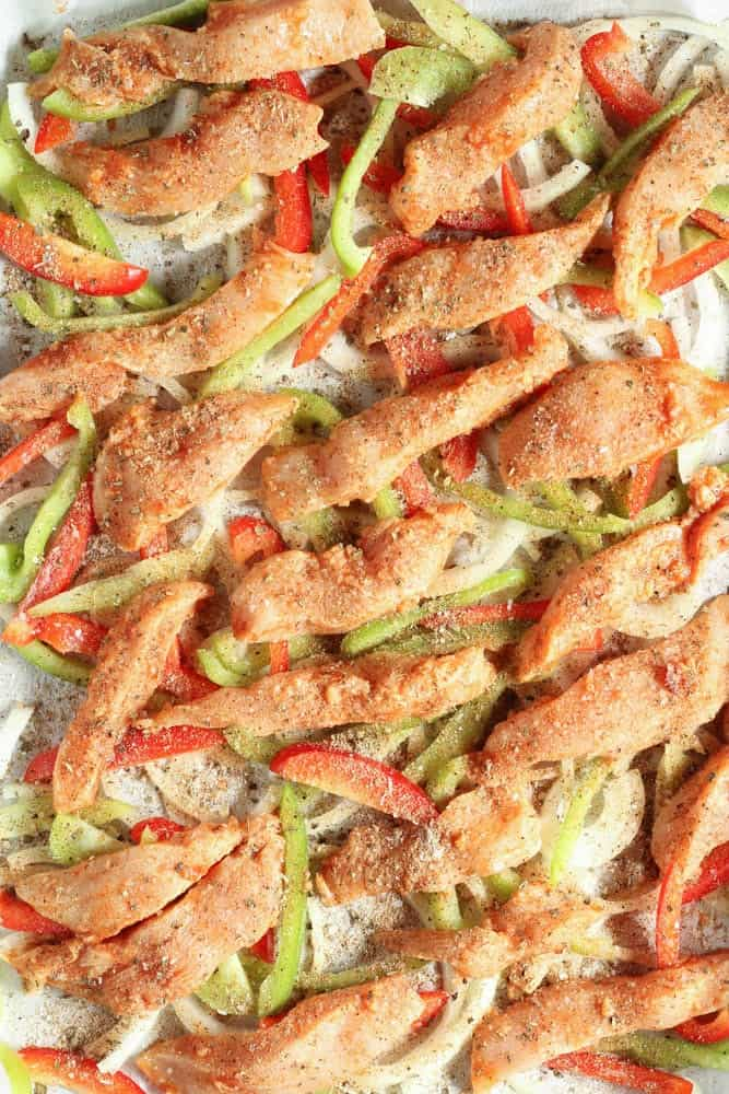 raw chicken and uncooked onions and peppers spread across a baking sheet lined with parchment paper sprinkled with herbs and spices