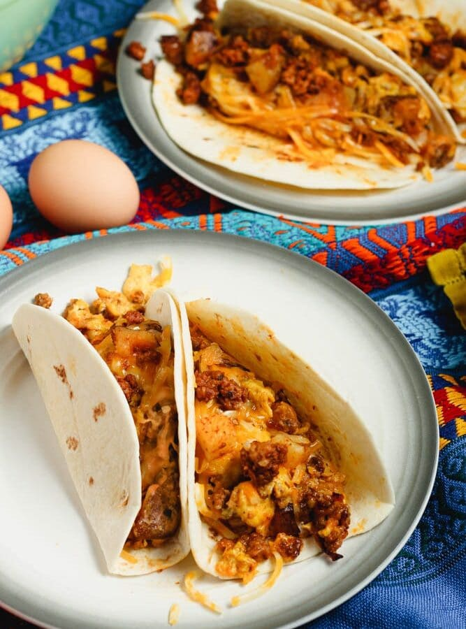 Two chorizo and potato breakfast tacos filled with orange chorizo, yellow scrambled eggs and chunks of potato and onion served in a flour tortilla on a white plate and a festive Mexican blanket backdrop