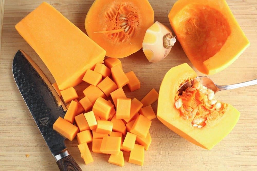 Light wooden cutting board with a split bright orange butternut squash, diced butternut squash, a spoon for scooping out the squash pulp and a chef's knife