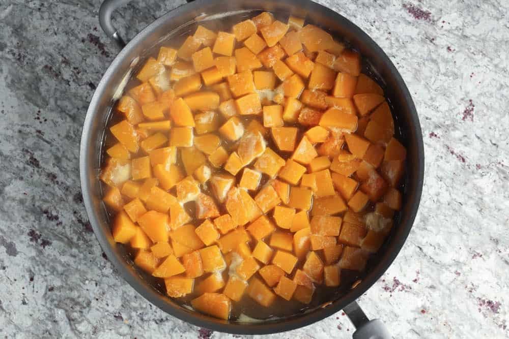 a large black high rimmed saute pan filled with bright orange butternut squash cut into one inch cubes and covered with chicken stock