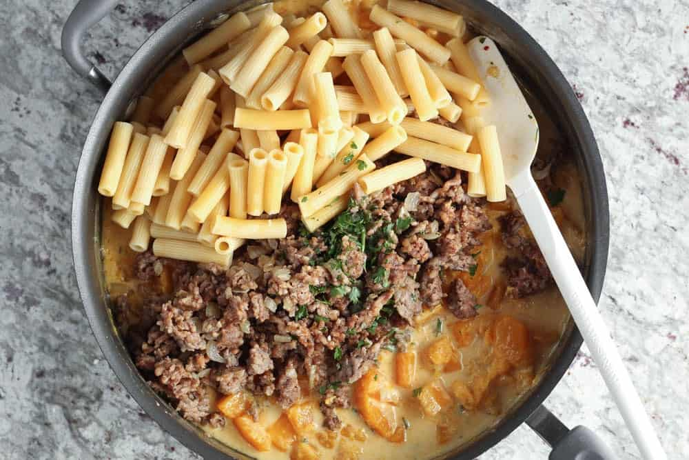 Large high rimmed saute pan filled with complete recipe before mixing together; one section contains cooked pasta, one the cooked sausage and onions mixture and last the bright orange cooked butternut squash