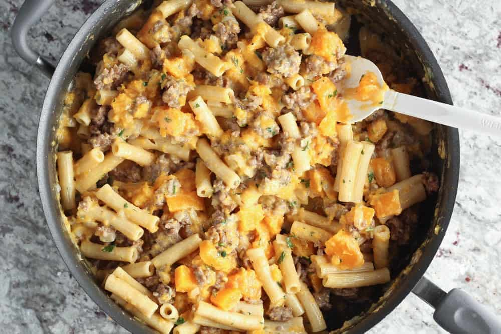 the completed recipe mixed together in a large high rimmed saute pan featuring butternut squash, rigatoni and sausage