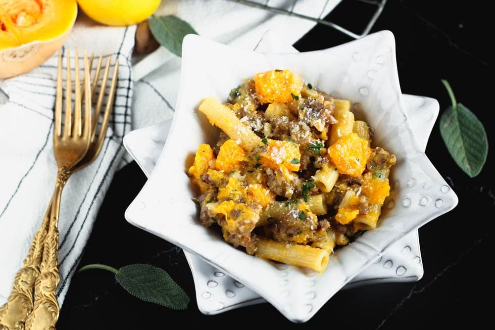 White star shaped bowl filled filled with orange butternut squash cubes, sausage pieces, rigatoni and fleck of white parmesan cheese and green chopped parsley