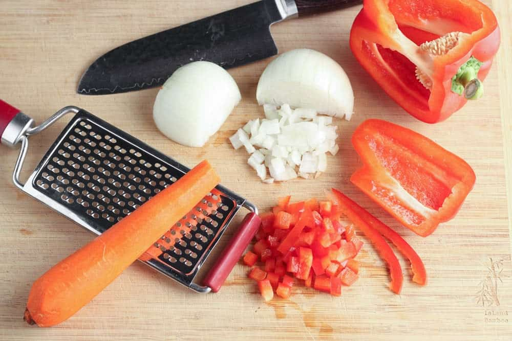 orange carrot, red bell pepper and white onion on a light wooden cutting board being prepared for recipe