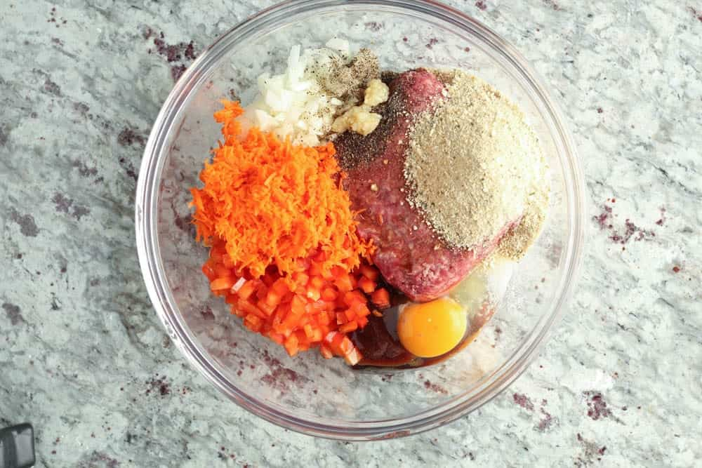 large glass bowl filled with meatloaf ingredients prior to mixing including grated orange carrot, diced red bell pepper and white onion, ground beef, breadcrumbs and a raw egg