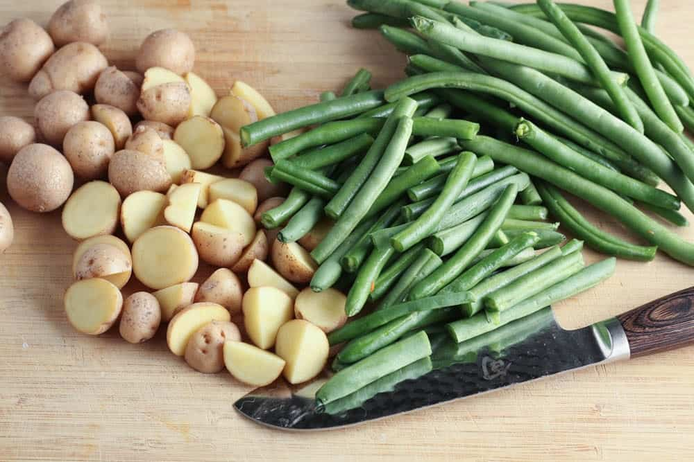 Light wooden cutting board with green beans and potatoes split in half