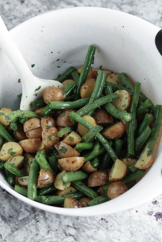 White mixing bowl filled with green beans and halved potatoes covered in a herb oil