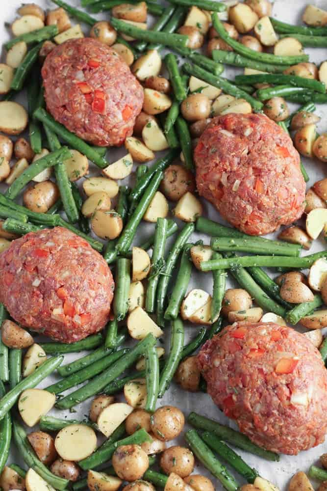 raw meatloaves on a piece of white parchment paper surrounded by green beans and potatoes