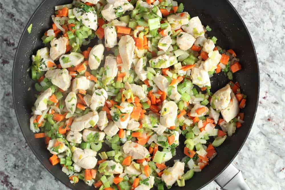 Diced chicken, carrots, celery, onions and parsley in a black saute pan