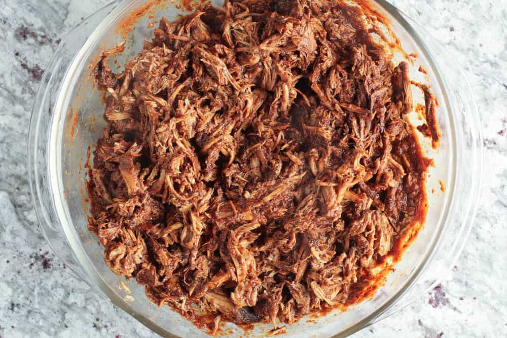 shredded pork shoulder covered in red mole sauce in a clear glass bowl