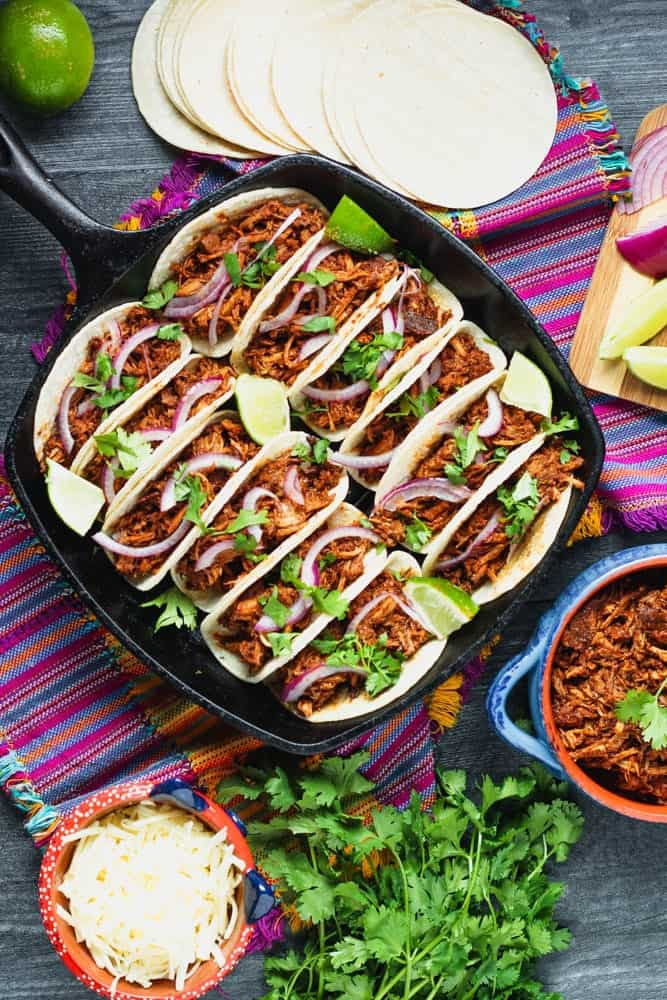 a dozen mole pulled pork tacos in a cast iron pan topped with red onions and cilantro surrounded by a bright purple napkin, cilantro leaves, corn tortillas and extra shredded pork in a blue bowl