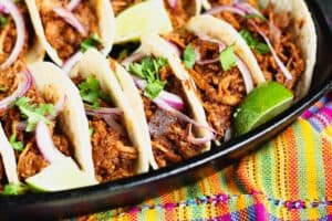 5 mole pork tacos topped with thinly sliced red onion, bright green cilantro and lime wedges on a dark black plate