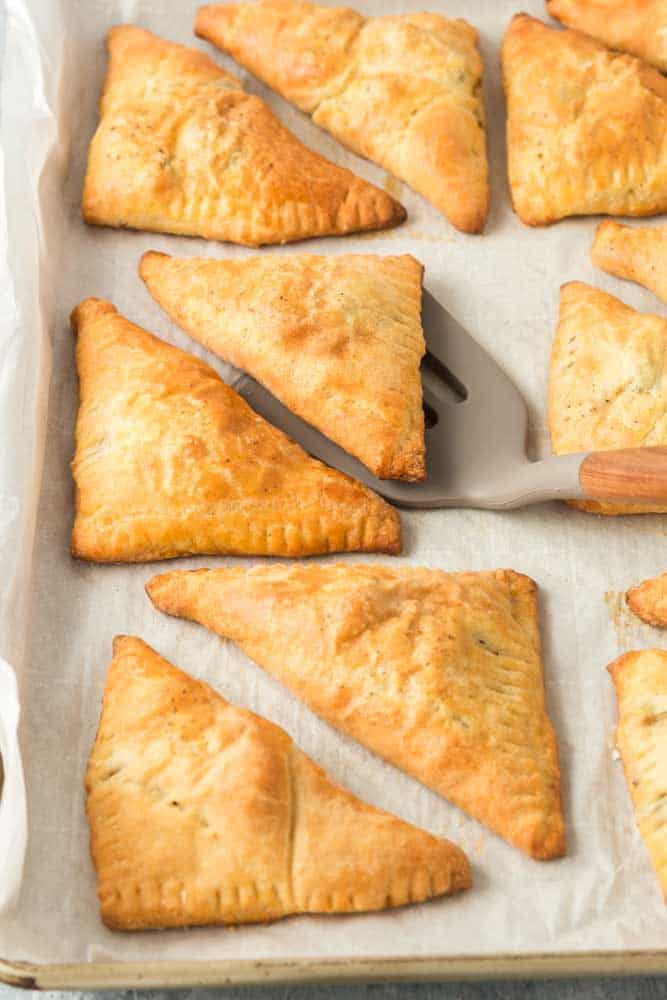 Louisiana Meat Pies on a parchment lined baking sheet with a spatula lifting one pie from the pan