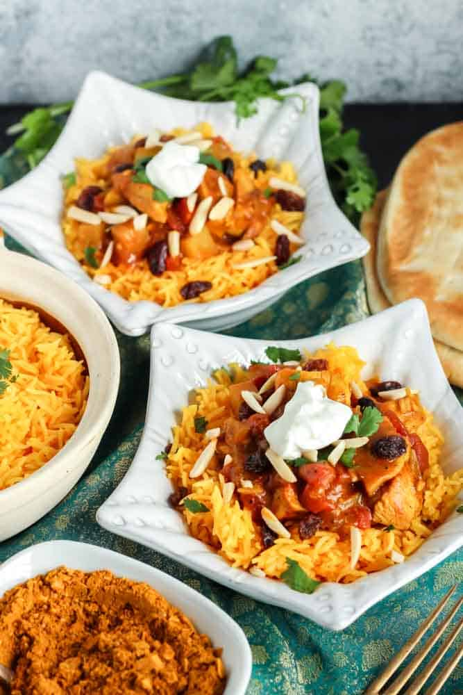 two star shaped dishes filled with orange rice and red chicken curry topped with green cilantro and white dollop of yogurt