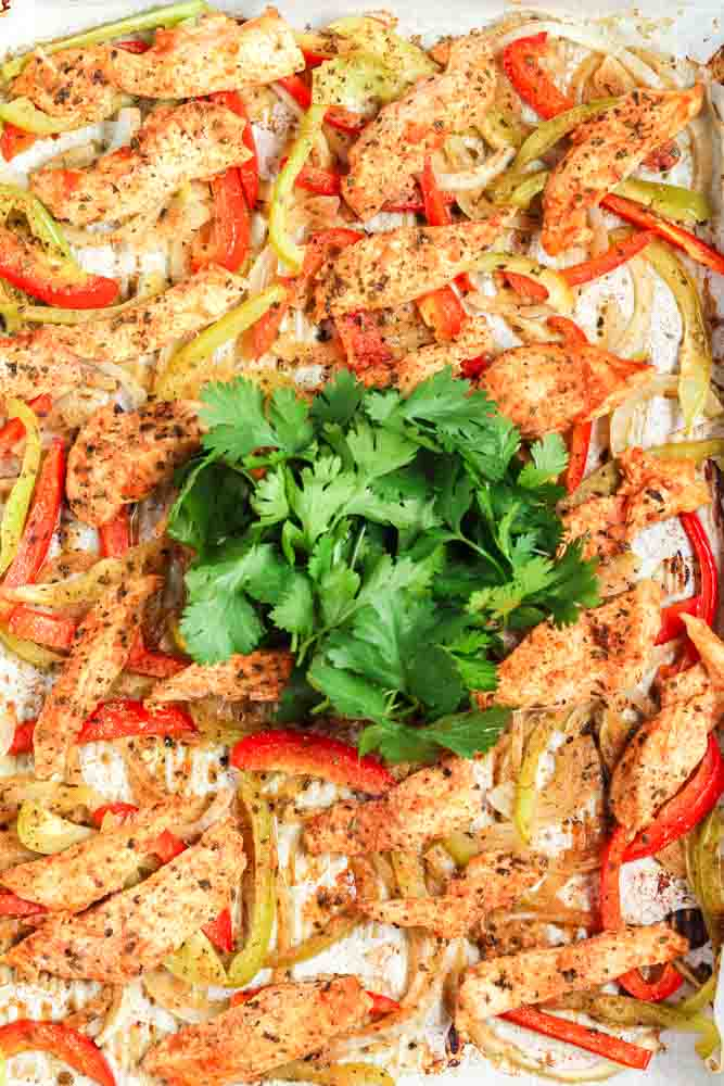 Sheet pan fajitas on a gold baking sheet lined with parchment paper topped with bright green cilantro