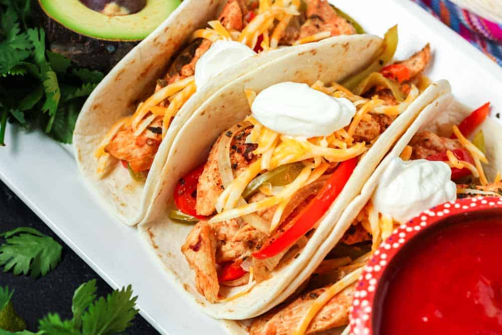 Three prepared chicken fajitas tacos with slices of chicken, peppers, onions, shredded cheese and a dollop of sour cream with a bowl of red salsa and fresh green avocadoes on the side