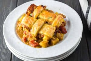 Chicken curry pot pie dished out onto a white plate featuring a golden brown lattice puff pastry topping