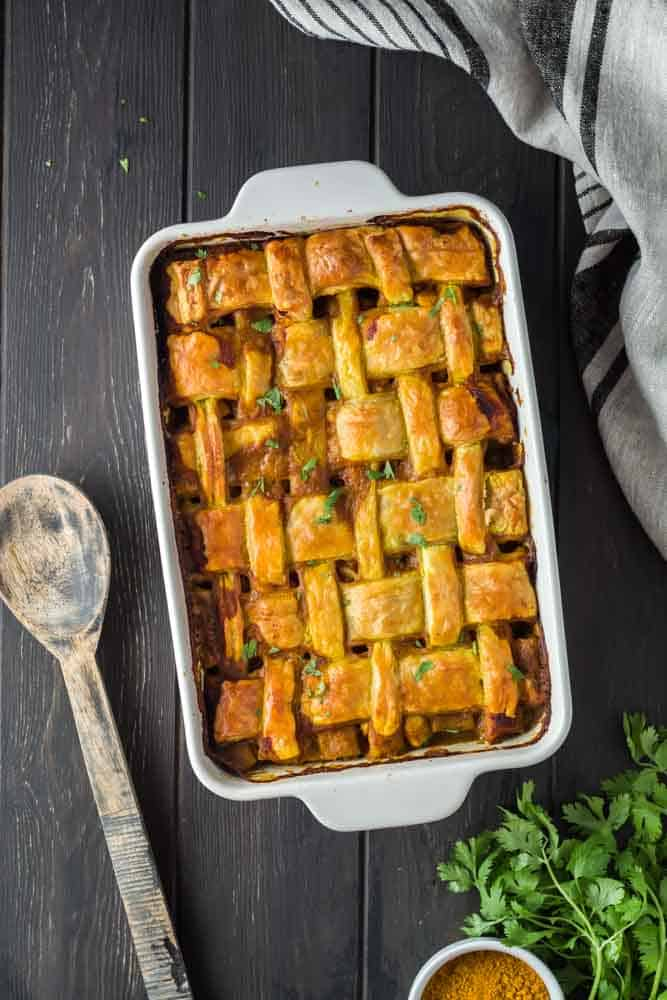 Chicken curry pot pie in a white baking dish featuring a golden brown lattice puff pastry topping