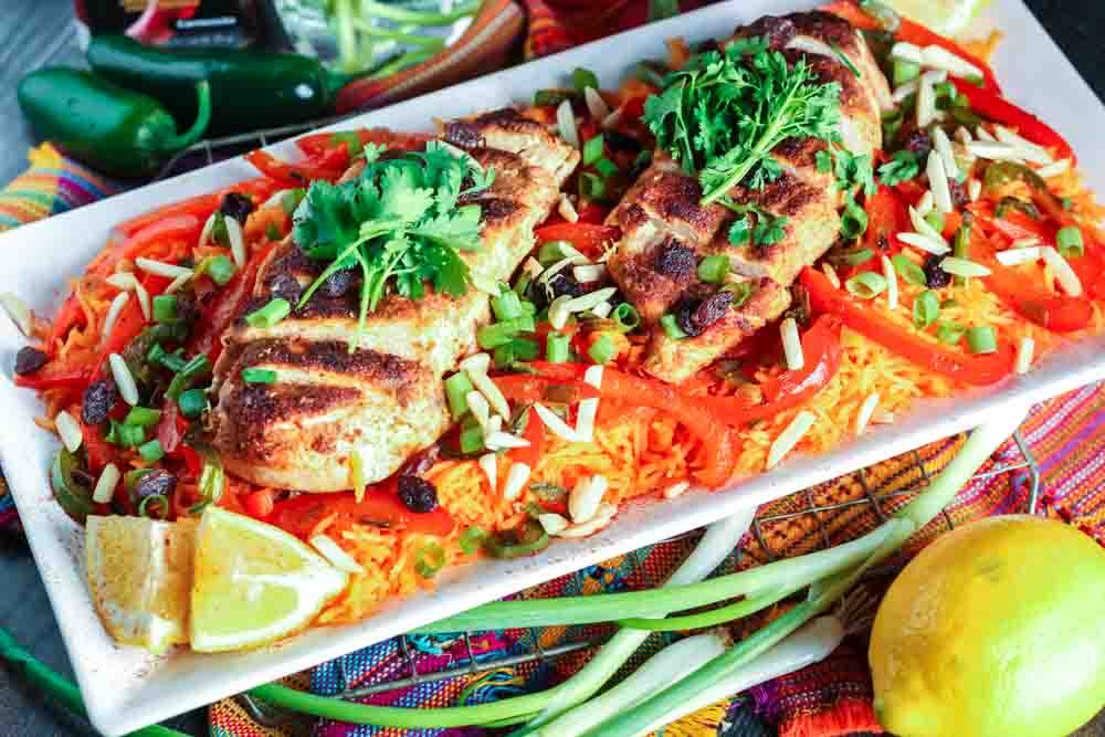white rectangular plate filled with orange rice topped with strips of red bell pepper, green onion pieces, sliced chicken breast and cilantro with a lemon wedge