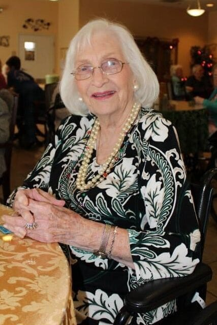 Elderly female smiling with her hands on a table