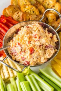 close up of silver bowl of orange pimento cheese surrounded by green celery sticks, red and yellow bell pepper strips and golden brown toasted baguette
