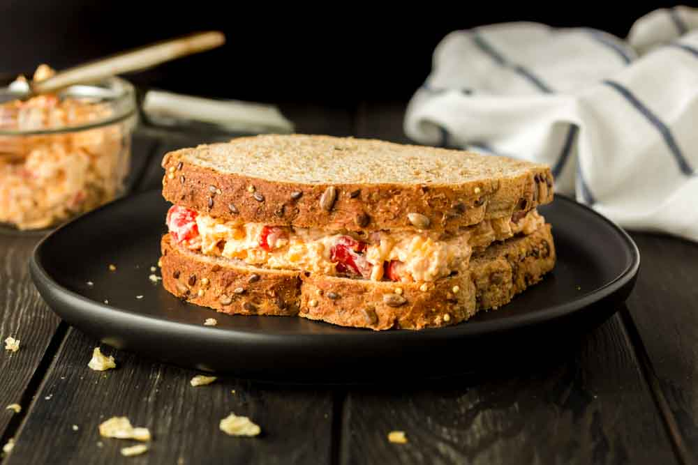 Pimento cheese sandwich on wheat bread on a black plate with bread crumbs on the board