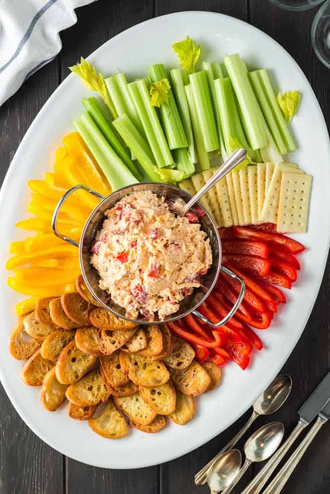 white oval shaped platter with a silver bowl of orange pimento cheese in the center surrounded by green celery sticks, red and yellow bell pepper strips and golden brown toasted baguette