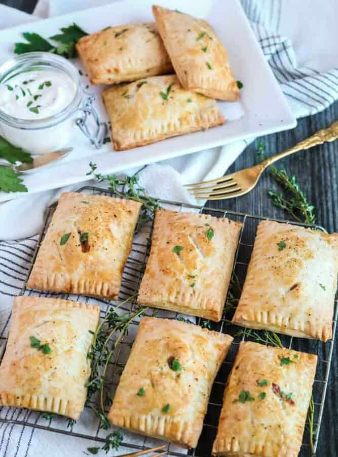 rectangular pastries garnished with green herbs on a wire rack