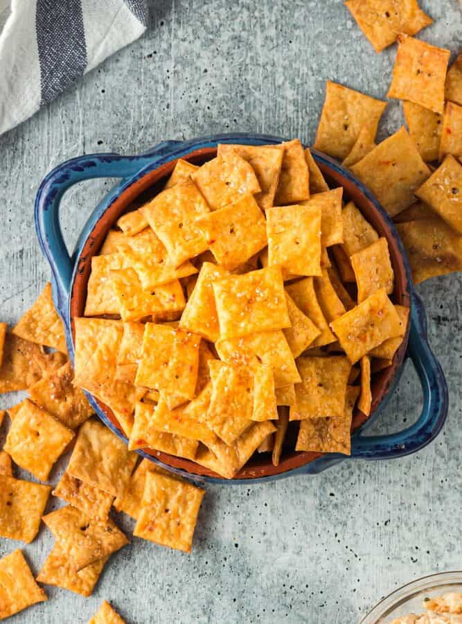 Bright orange square crackers with a single hole in the middle spilling out of a bright blue bowl