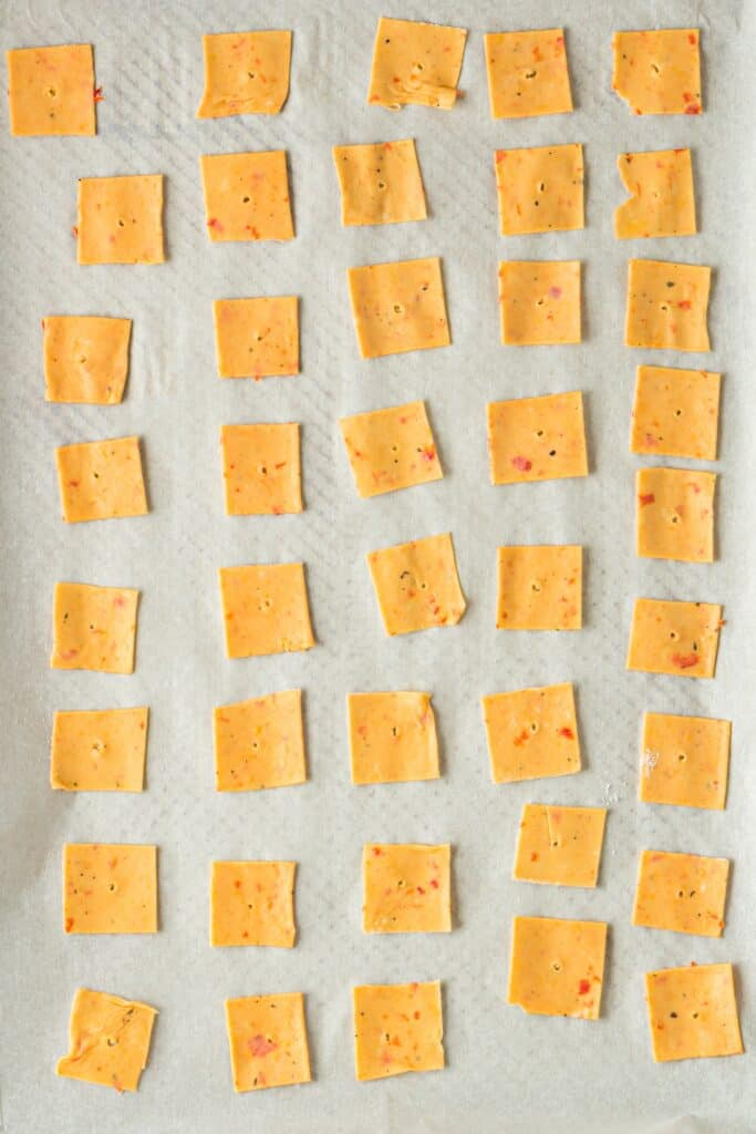 Uncooked bright orange dough cut into squares and laid on white parchment paper