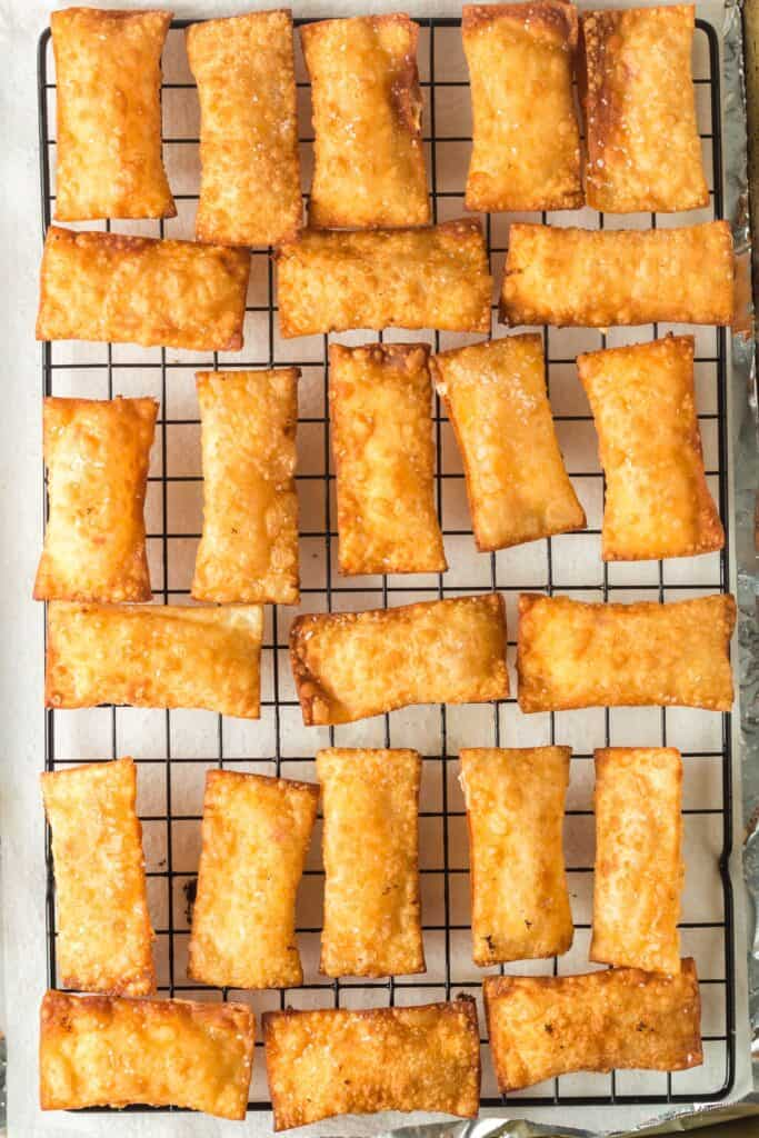 Golden brown rectangular pimento cheese wontons on a cooling rack