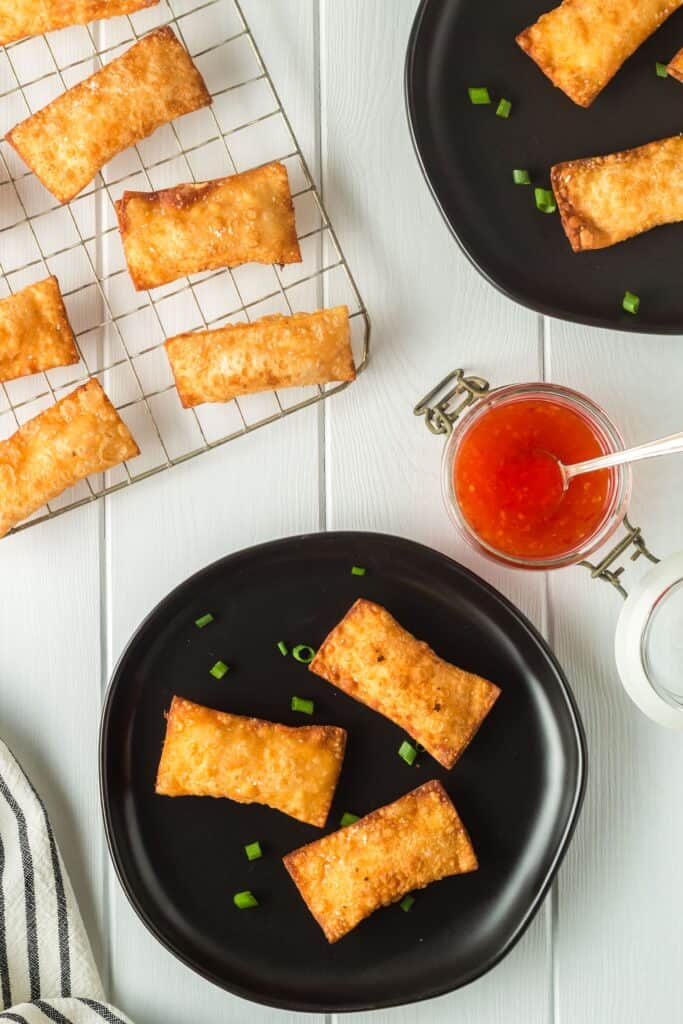 Golden brown rectangular pimento cheese wontons on small black plate and a cooling rack with a side of bright red thai sweet chili dipping sauce