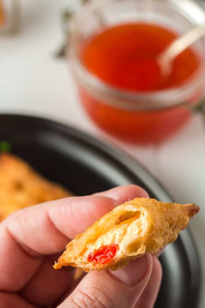 Closeup of inside of pimento cheese wonton showing the gooey melted pimento cheese filling