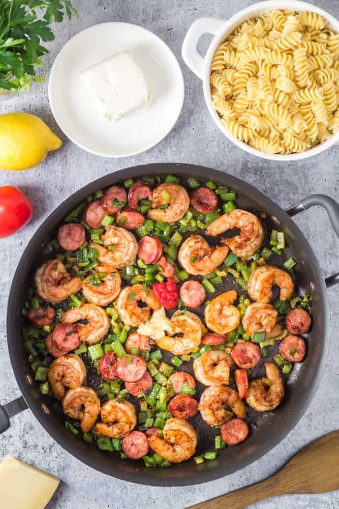 Sauteed shrimp and andouille sauage with green onions surrounded by small bowl of cream cheese and a strainer of cooked pasta
