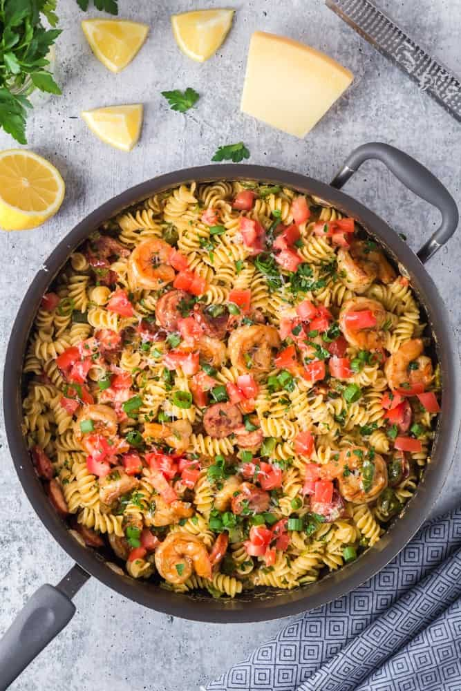 Large black saute pan filled with Cajun Shrimp Pasta with rotini pasta, andouille sausage rounds, bright red tomatoes and bell peppers and sliced green onions