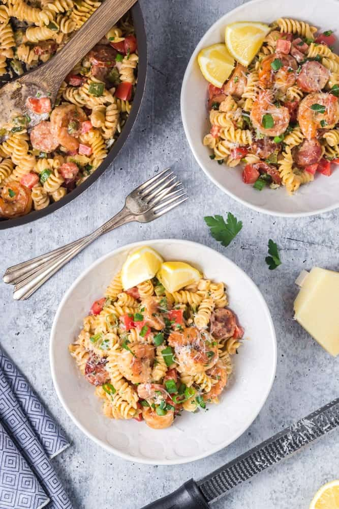 Two white bowls filled with Cajun Shrimp Pasta with rotini pasta, andouille sausage rounds, bright red tomatoes and bell peppers and sliced green onions