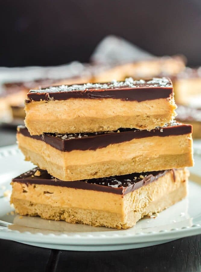 Three Chocolate Peanut Butter Bar squares on a small white plate- the squares are made up of a base layer of peanut butter cookie, topped with smooth peanut butter filling and topped with a shiny chocolate ganache and flakes of sea salt