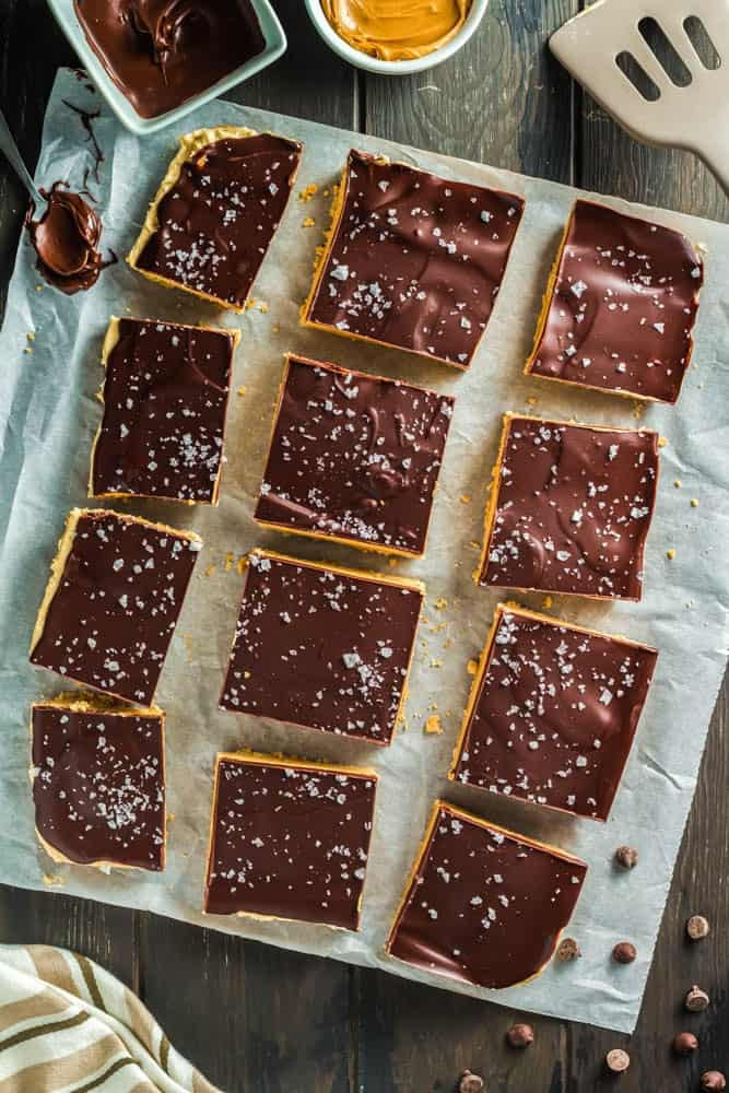 Chocolate Peanut Butter Bars made up of a base layer of peanut butter cookie, topped with smooth peanut butter filling and topped with a shiny chocolate ganache and flakes of sea salt cut into twelve squares on a piece of parchment paper