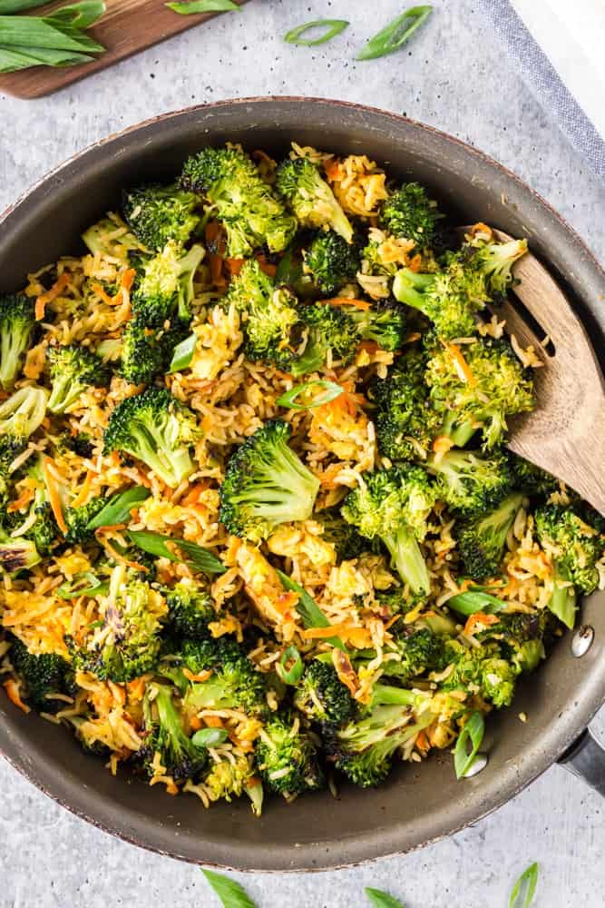 Saute pan filled with bright green broccoli florets, grated carrots, sliced green onions and fried rice