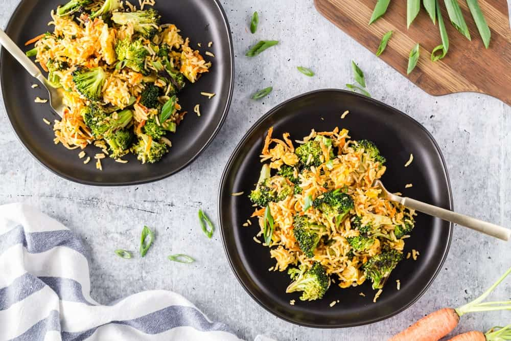 Two black plates filled with bright green broccoli florets, grated carrots, sliced green onions and fried rice