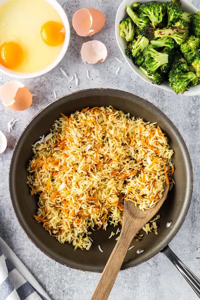 rice and and grated carrots in a saute pan being fried with two eggs cracked into a small bowl and a bowl of green roasted broccoli on the side