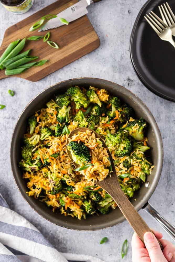 Saute pan filled with bright green broccoli florets, grated carrots, sliced green onions and fried rice with a spoon scooping out a heap